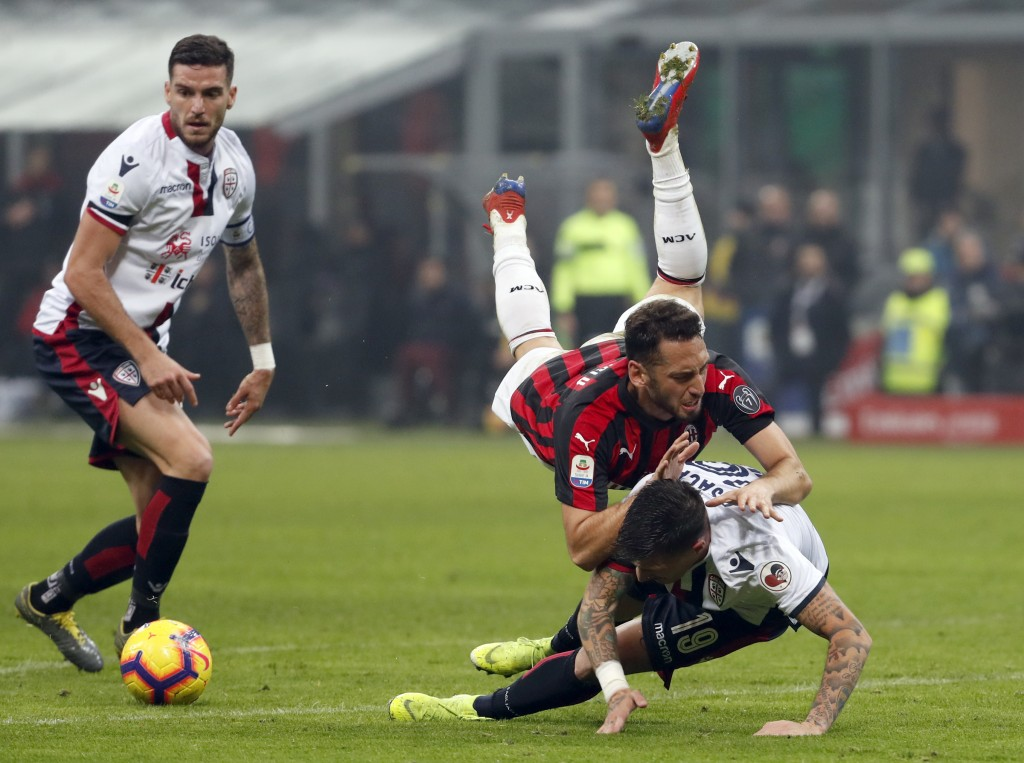 AC Milan's Hakan Calhanoglu and Cagliari's Fabio Pisacane challenge for the ball during the Serie A soccer match between AC Milan and Cagliari at the ...