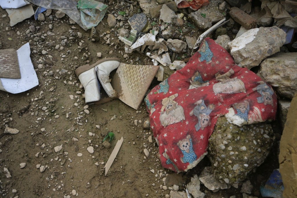 In this Jan. 18, 2019 photo, a child's boot and blanket lie in the ruins of a Christian house destroyed during fighting with the Islamic State group, ...