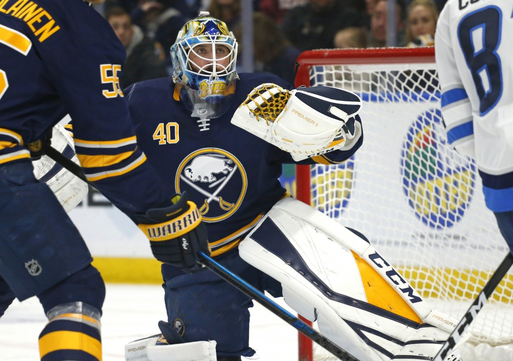 Buffalo Sabres goalie Carter Hutton (40) makes a glove-save during the first period of an NHL hockey game against the Winnipeg Jets, Sunday, Feb. 10, ...