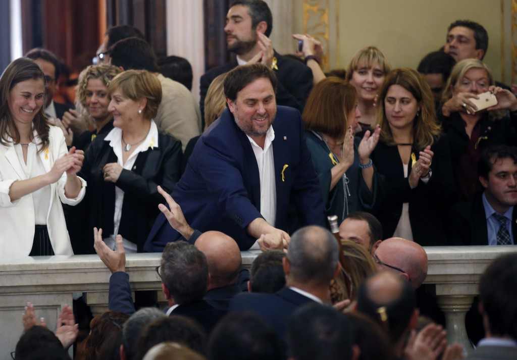 FILE - In this Friday, Oct. 27, 2017 file photo, Catalan Vice President Oriol Junqueras, center, is greeted after a vote on independence in the Catala...