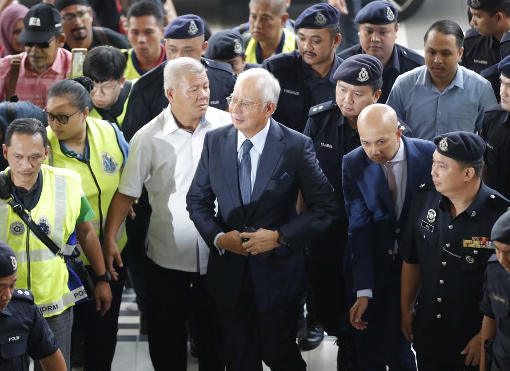 FILE - In this Oct. 4, 2018, file photo, former Malaysian Prime Minister Najib Razak, center, arrives at Kuala Lumpur High Court in Kuala Lumpur, Mala