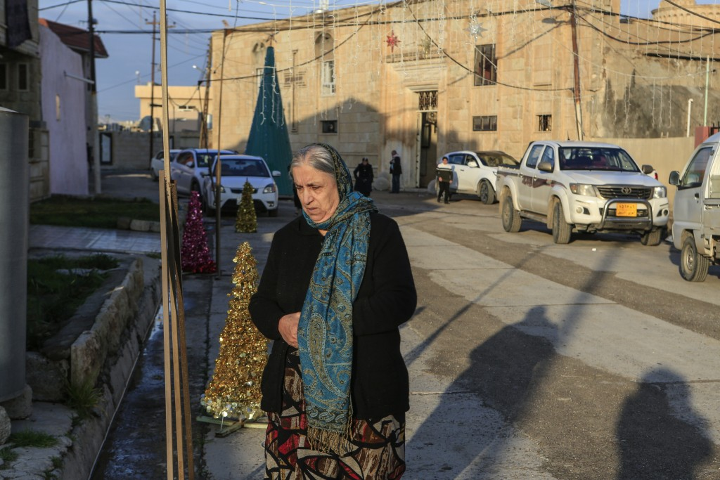 In this Jan. 18, 2019 photo, a woman walks in from of the Mart Shmony Orthodox Church in Bartella, Iraq. Two years after it was liberated from Islamic