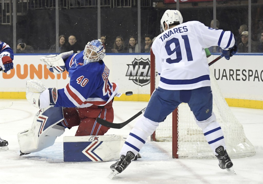 New York Rangers goaltender Alexandar Georgiev (40) eyes the puck as Toronto Maple Leafs center John Tavares (91) attempts to get his stick on the puc...