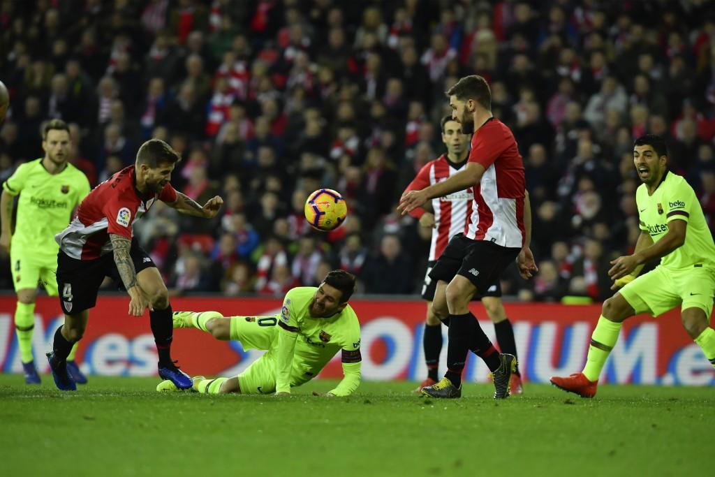 FC Barcelona's Lionel Messi, falls beside Athletic Bilbao's Inigo Martinez, left, during the Spanish La Liga soccer match between Athletic Bilbao and