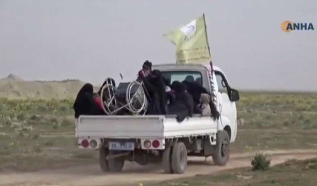 In this Sunday, Feb. 10, 2019 image from video provided by Hawar News Agency, ANHA, an online Kurdish news service, civilians flee fighting near Bagho...