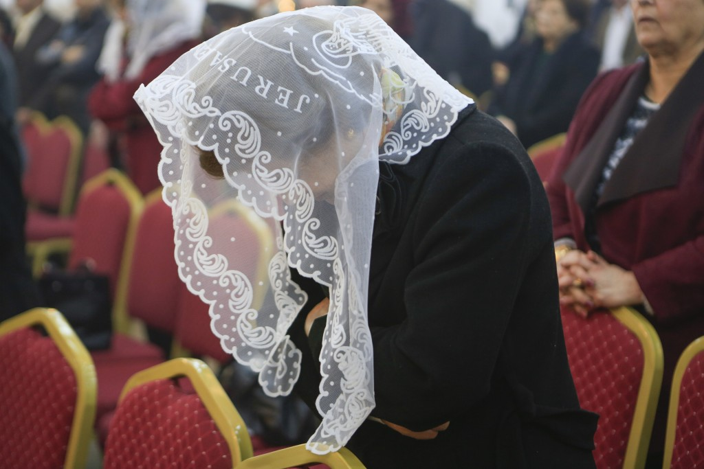 In this Jan. 20, 2019 photo, a woman prays during  Sunday service at Mart Shmony Orthodox Church the northern town of Irbil, Iraq. Two years after it