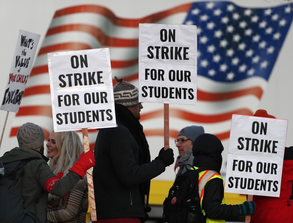 Teachers carry placards as they walk a picket line outside South High School early Monday, Feb. 11, 2019, in Denver. The strike on Monday is the first