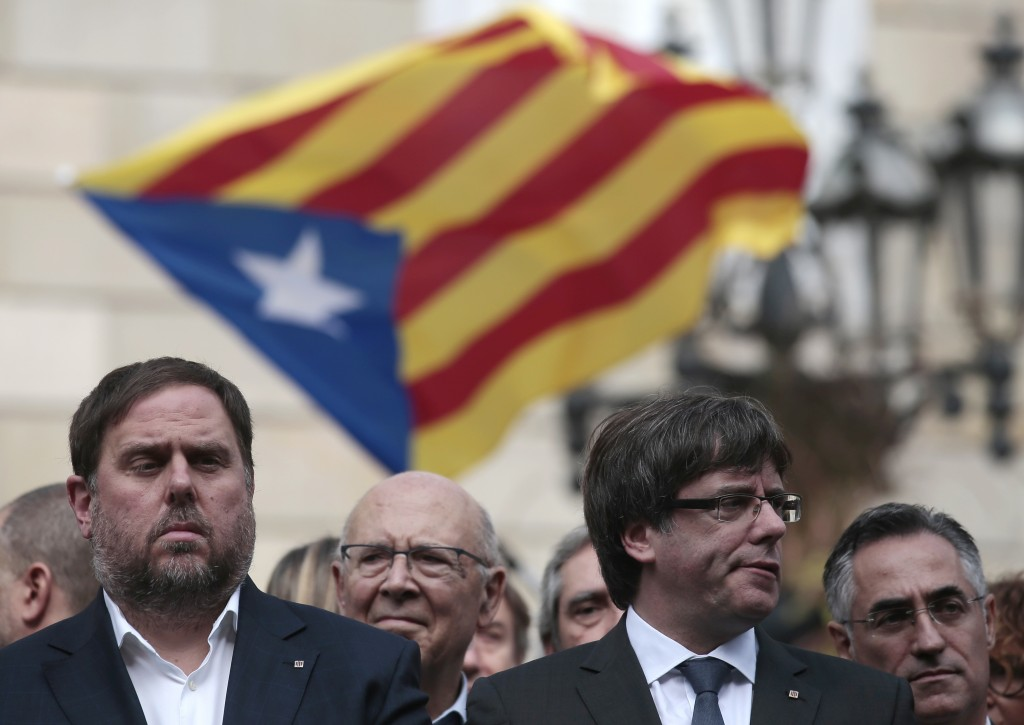 FILE - In this Monday, Oct. 2, 2017 file photo, Catalan regional Vice-President, Oriol Junqueras, left, and Catalan President, Carles Puigdemont, atte...