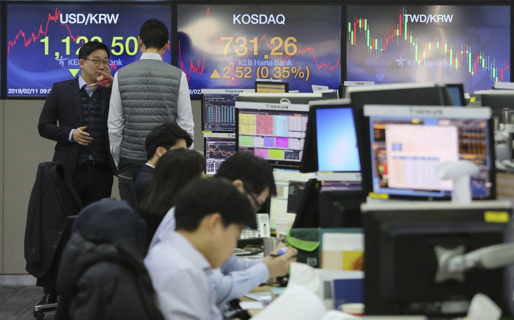 Currency traders work at the foreign exchange dealing room of the KEB Hana Bank headquarters in Seoul, South Korea, Monday, Feb. 11, 2019. Asian stock...