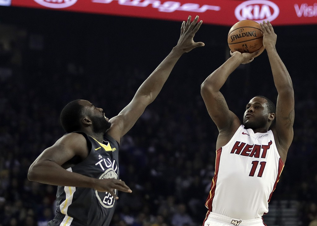 Miami Heat guard Dion Waiters, right, shoots against Golden State Warriors' Draymond Green, left, during the first half of an NBA basketball game day,...