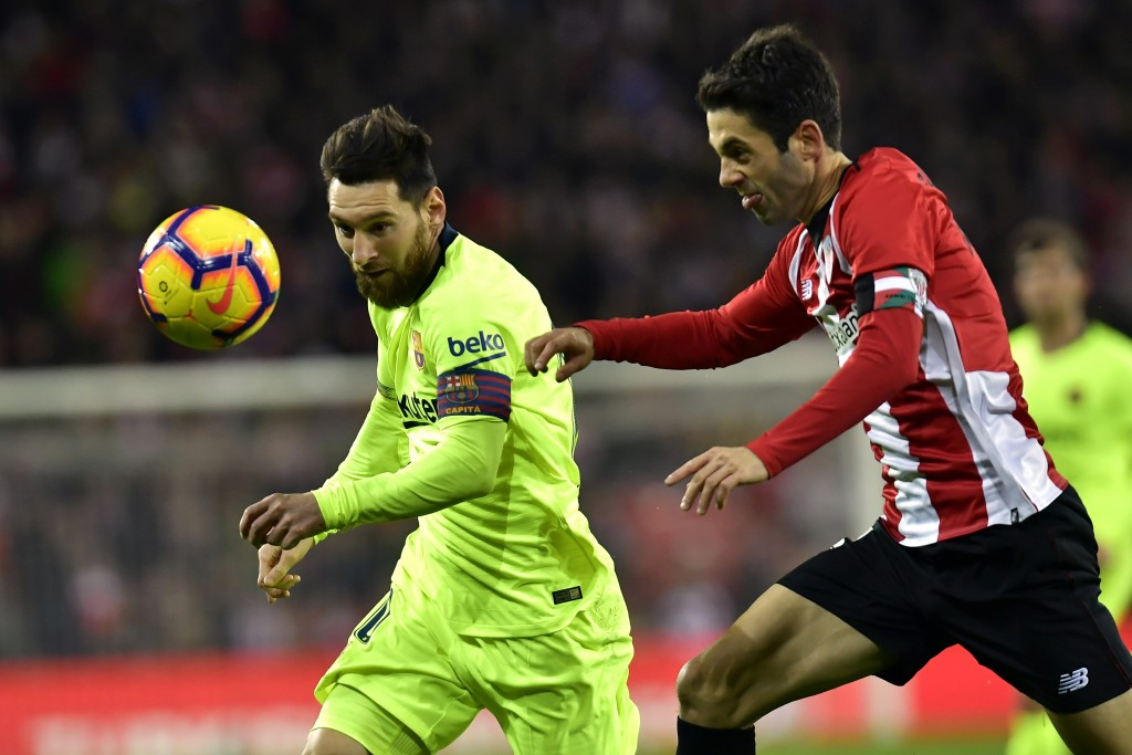 FC Barcelona's Lionel Messi, left, duels for the ball beside Athletic Bilbao's Markel Susaeta during the Spanish La Liga soccer match between Athletic