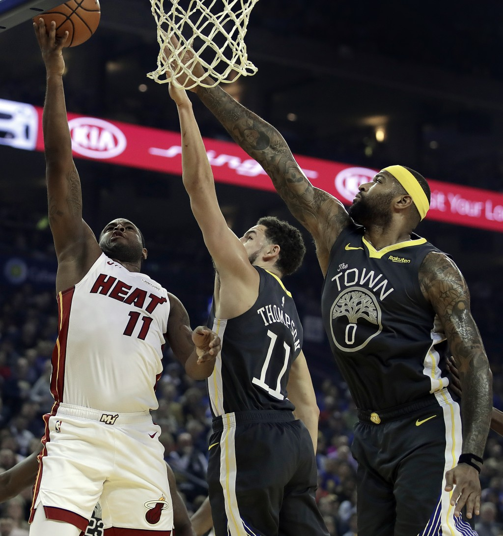 Miami Heat guard Dion Waiters, left, shoots against Golden State Warriors' Klay Thompson, center, and DeMarcus Cousins (0) during the first half of an