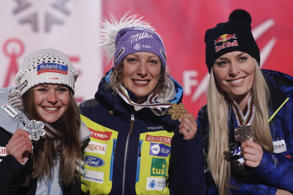From left, second placed Corinne Suter of Switzerland, winner Ilka Stuhec of Slovenia, and third placed Lindsey Vonn of the United States pose during ...