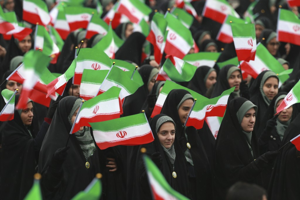 Iranians wave national flags during a ceremony celebrating the 40th anniversary of the Islamic Revolution, at the Azadi, or Freedom, Square, in Tehran