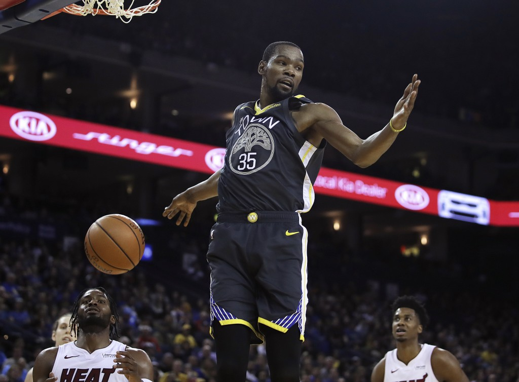 Golden State Warriors' Kevin Durant (35) scores against the Miami Heat during the second half of an NBA basketball game, Sunday, Feb. 10, 2019, in Oak
