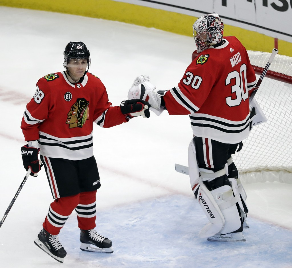 Chicago Blackhawks right wing Patrick Kane, left, celebrates with goalie Cam Ward after scoring a goal against the Detroit Red Wings during the third