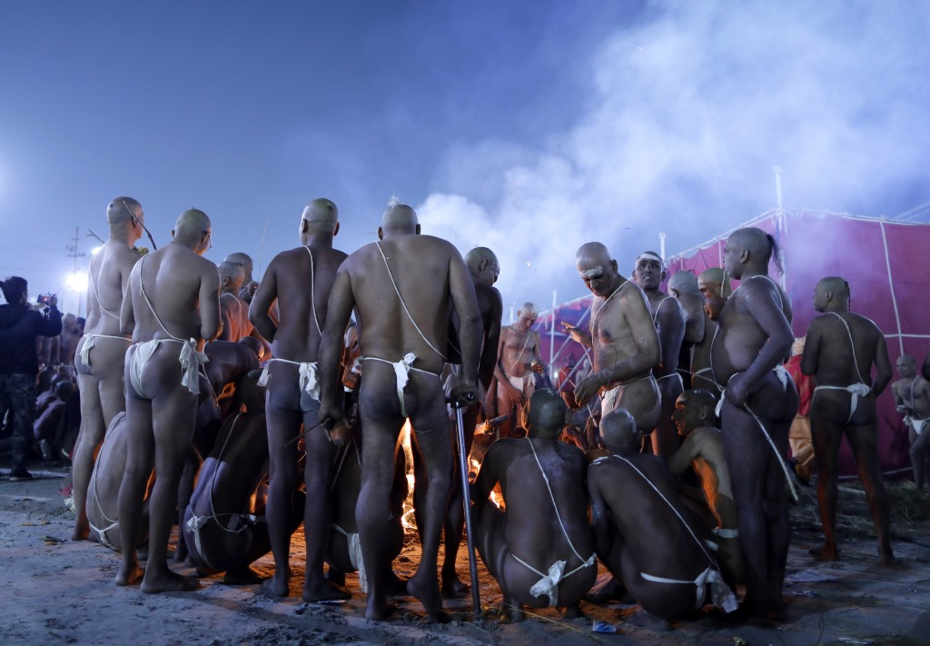 In this Jan. 27, 2019, photo, Hindu men warm themselves around a bonfire after taking a dip during a process for becoming Naga Sadhus or naked holy me