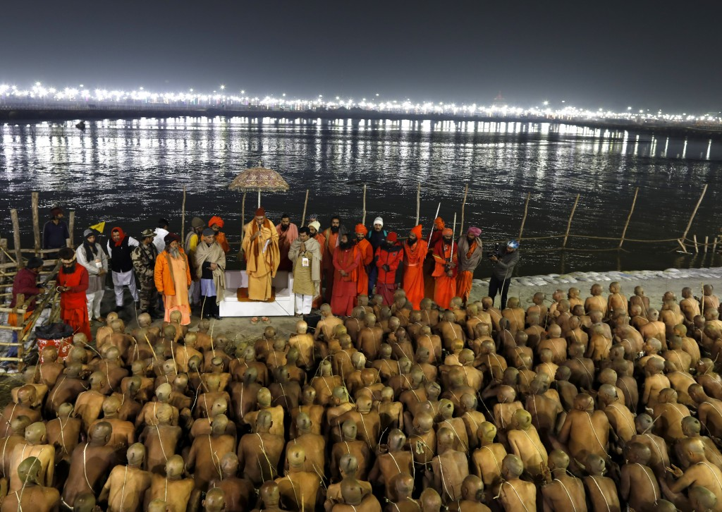 In this Jan. 28, 2019, photo, a high priest initiates the process of becoming Naga Sadhus or naked holy men at Sangam, the confluence of three holy ri...