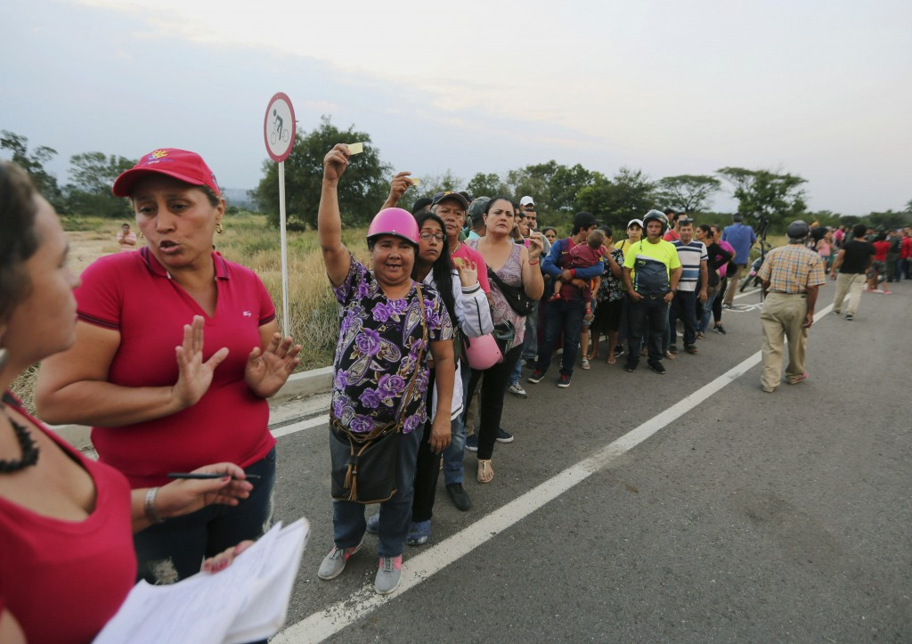 People show their tickets to received a bag with food subsidized by the Nicolas Maduro's government near the international bridge of Tienditas on the ...