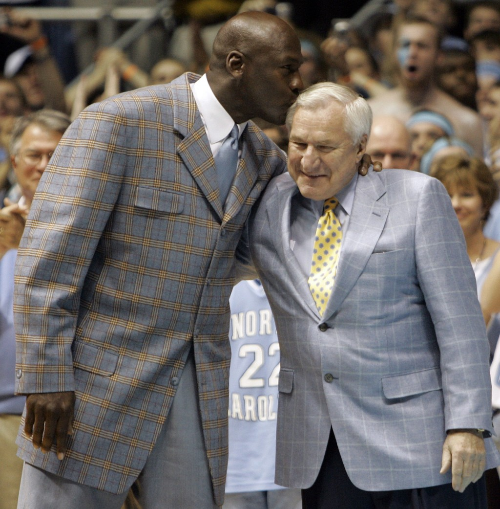 File-This Feb. 10, 2007, file photo shows former North Carolina player Michael Jordan, left, giving his former coach Dean Smith a kiss during halftime