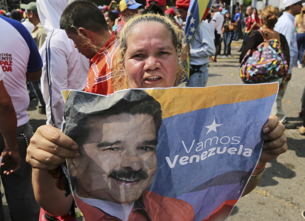 A supporter of Venezuela's President Nicolas Maduro holds a poster of him during a rally in Urena, Venezuela, Monday, Feb. 11, 2019. Nearly three week