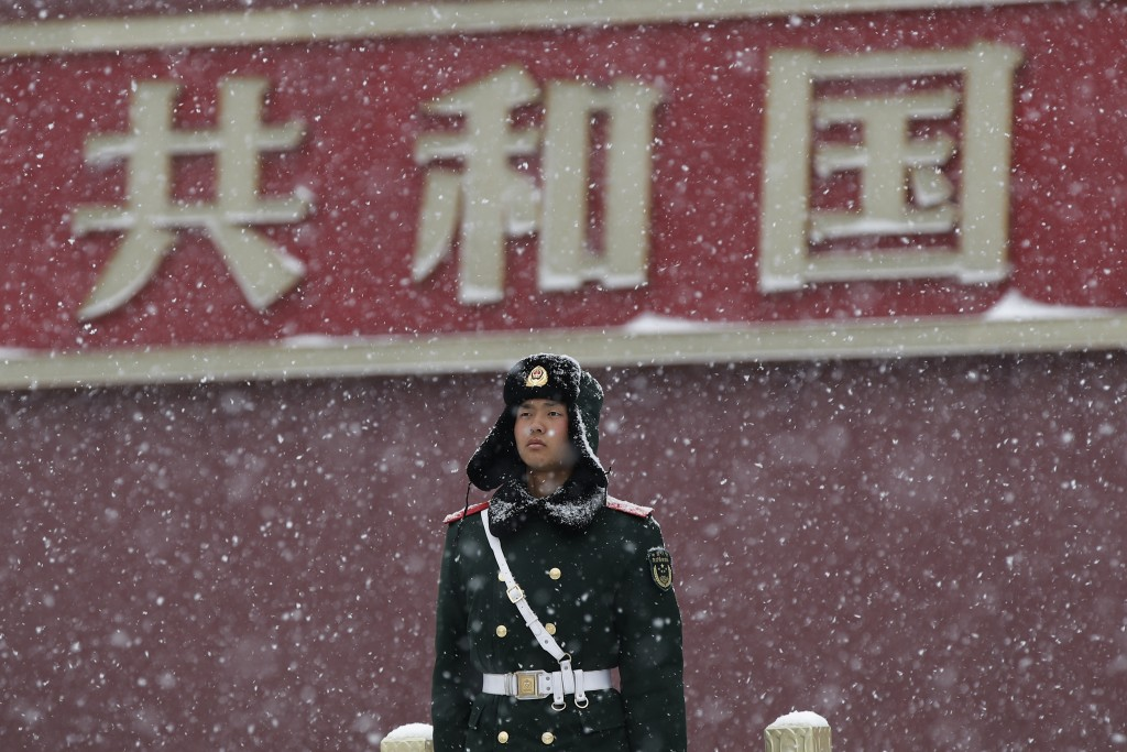 In this Tuesday, Feb. 12, 2019, file photo, a paramilitary policeman stands guard outside the Tiananmen Gate as snow falls in Beijing. China's capital...