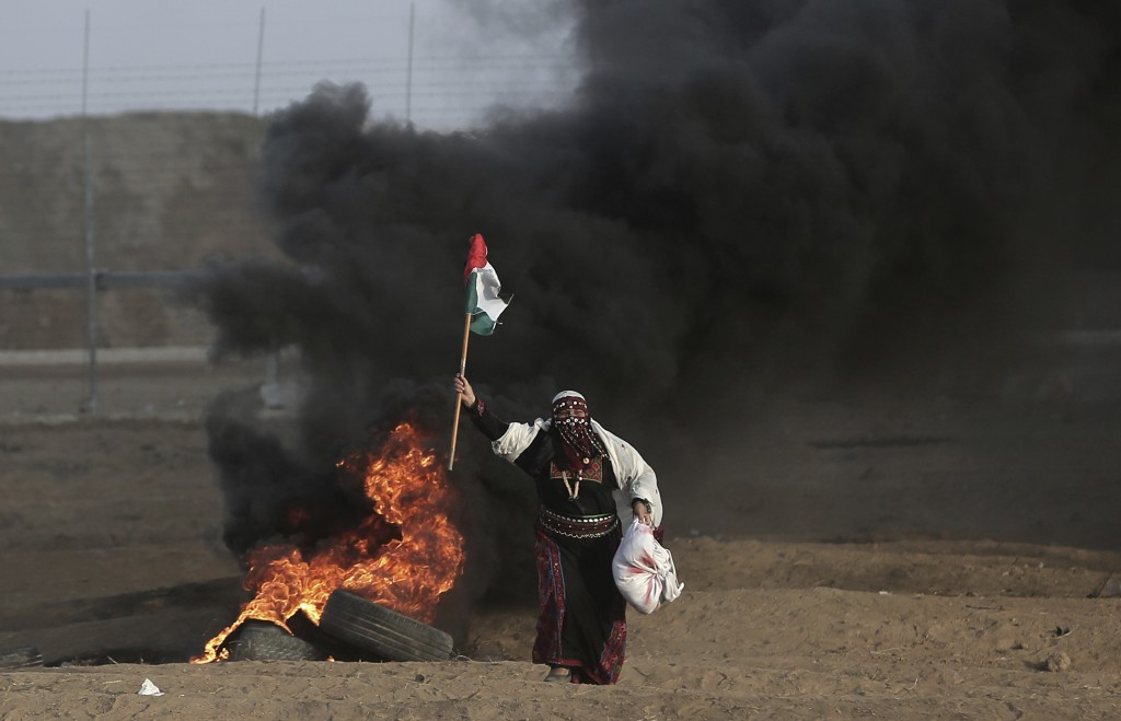 FILE - In this Oct. 5, 2018 file photo, a Palestinian woman wearing a traditional thobe, carries a Palestinian flag during a protest at the Gaza Strip...