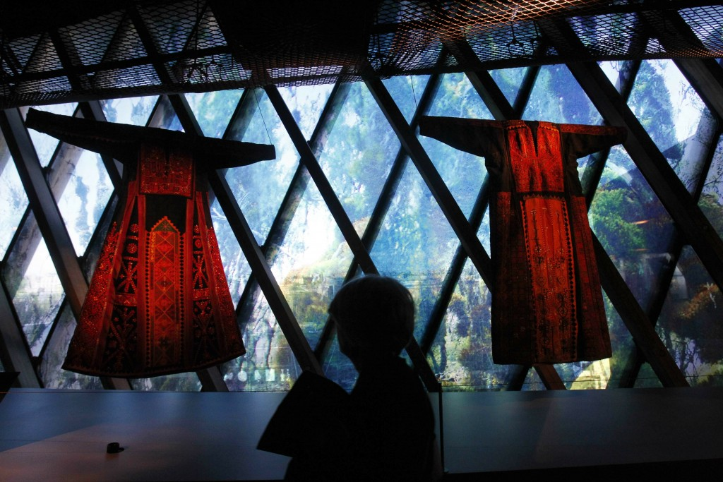 "FILE - In this Feb. 7, 2011 file photo, a woman views traditional Palestinian thobes during the exhibition ""Women in Orient"" at the Quai Branly Museum..."