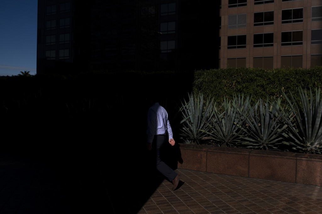 FILE- In this Dec. 4, 2018, file photo a man walks into the shade of a building in downtown Los Angeles. When deciding whether to buy, skip or toss an