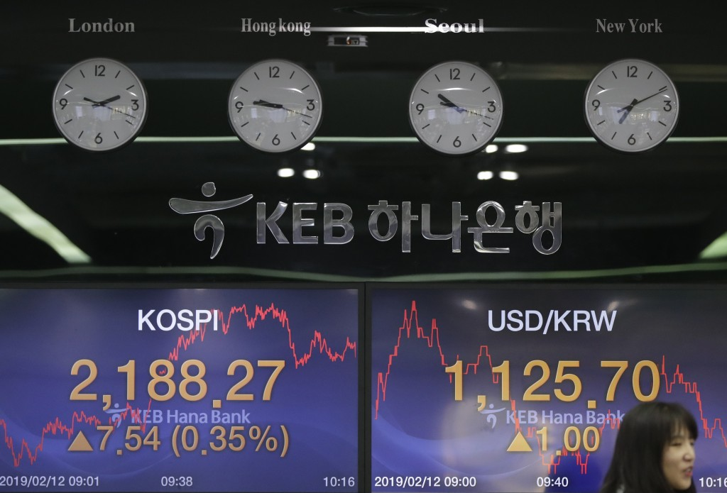 A currency trader talks near the screens showing the Korea Composite Stock Price Index (KOSPI), left, and the foreign exchange rate between U.S. dolla