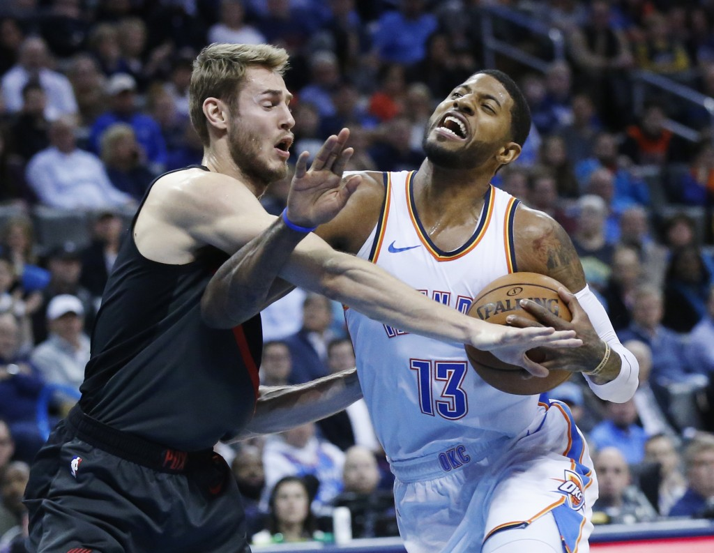 Oklahoma City Thunder forward Paul George (13) is fouled by Portland Trail Blazers forward Jake Layman, left, as he drives to the basket in the first