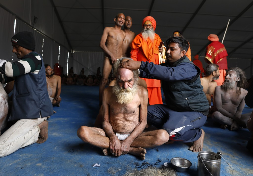 In this Jan. 27, 2019, photo, Hindu men get their hair cut in a ritual before becoming Naga Sadhus or naked holy men at Sangam, the confluence of thre...