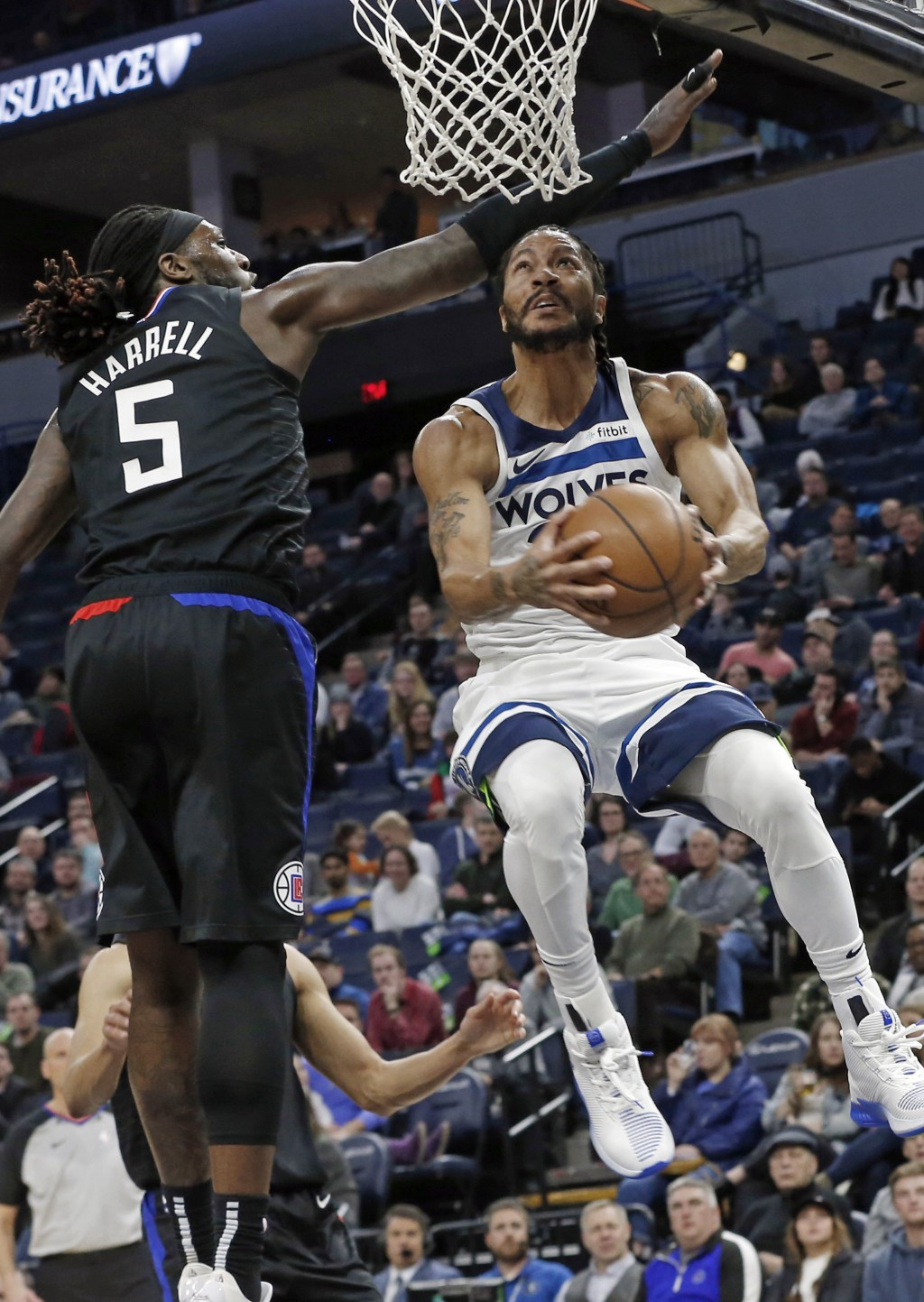 Minnesota Timberwolves' Derrick Rose, right, eyes the basket on a layup as Los Angeles Clippers' Montrezl Harrell defends in the first half of an NBA
