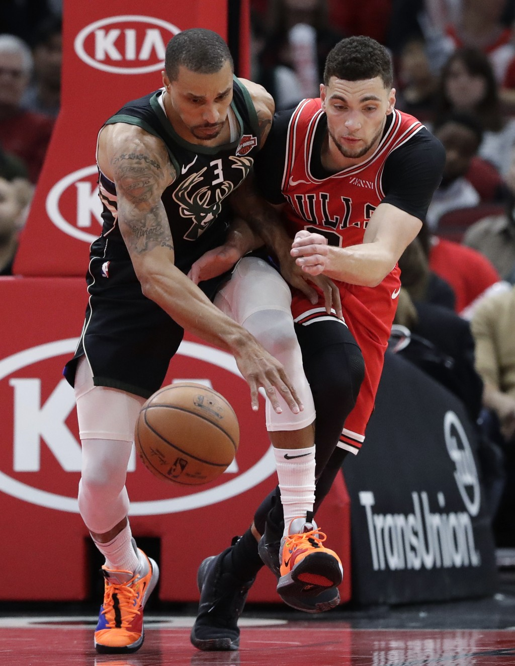 Milwaukee Bucks guard George Hill, left, battles for a loose ball against Chicago Bulls guard Zach LaVine during the first half of an NBA basketball g...