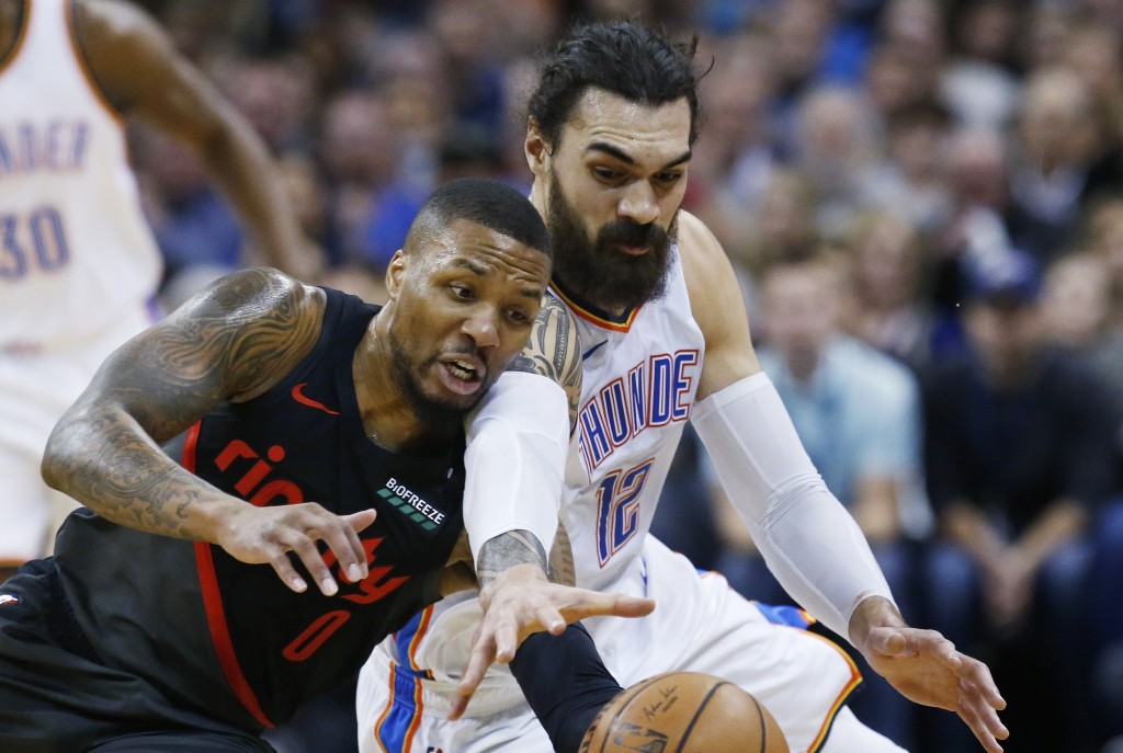 Portland Trail Blazers guard Damian Lillard (0) and Oklahoma City Thunder center Steven Adams (12) reach for the ball in the first half of an NBA bask