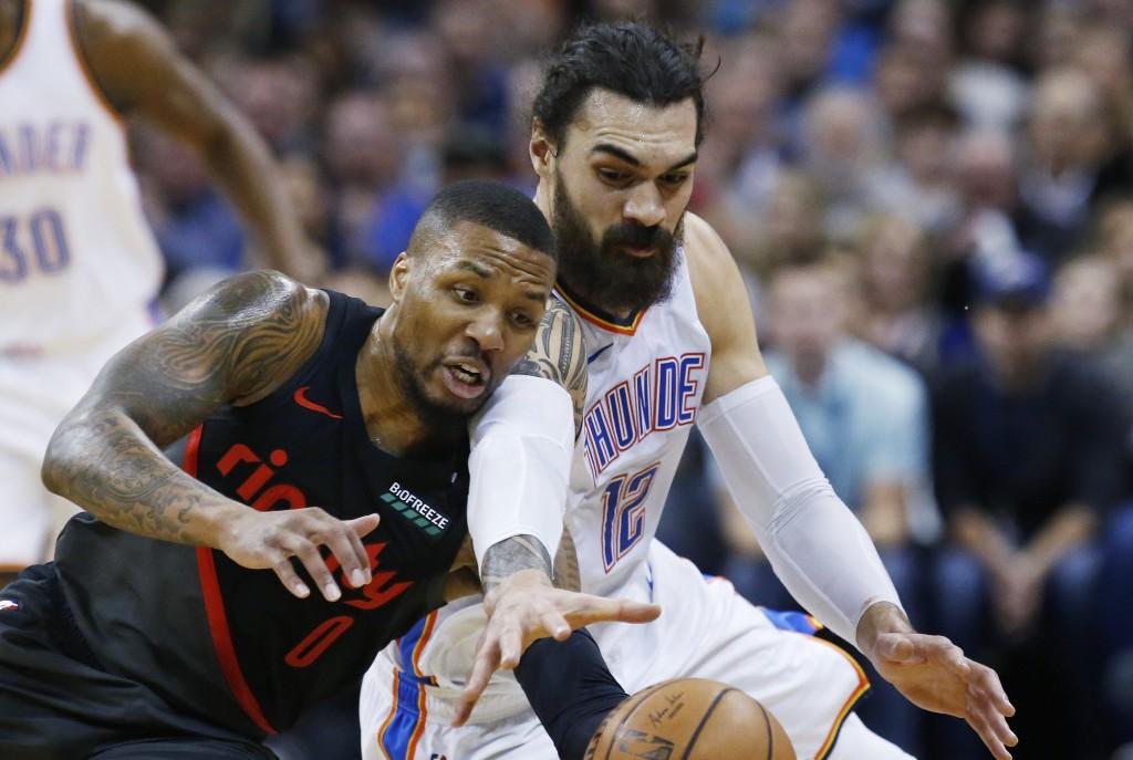 Portland Trail Blazers guard Damian Lillard (0) and Oklahoma City Thunder center Steven Adams (12) reach for the ball in the first half of an NBA bask...