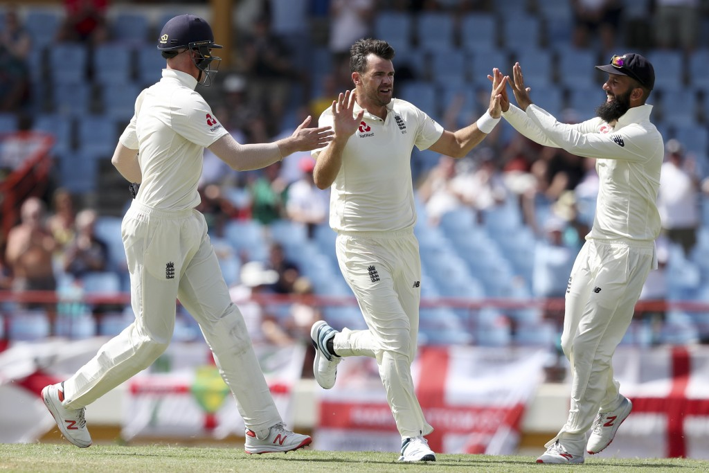 England's James Anderson celebrates taking the wicket of West Indies' captain Kraigg Brathwaite with teammates Moeen Ali, right, and Keaton Jennings d...