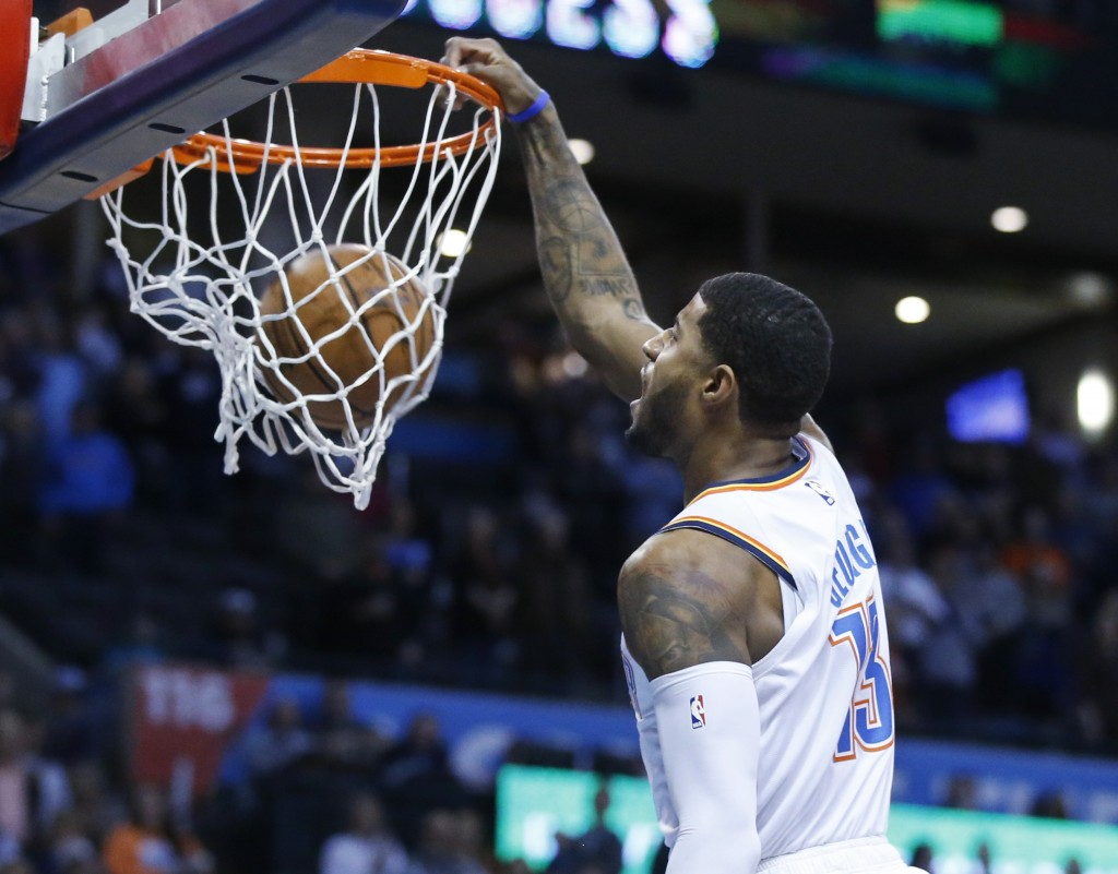 Oklahoma City Thunder forward Paul George (13) dunks in the first half of an NBA basketball game against the Portland Trail Blazers in Oklahoma City,