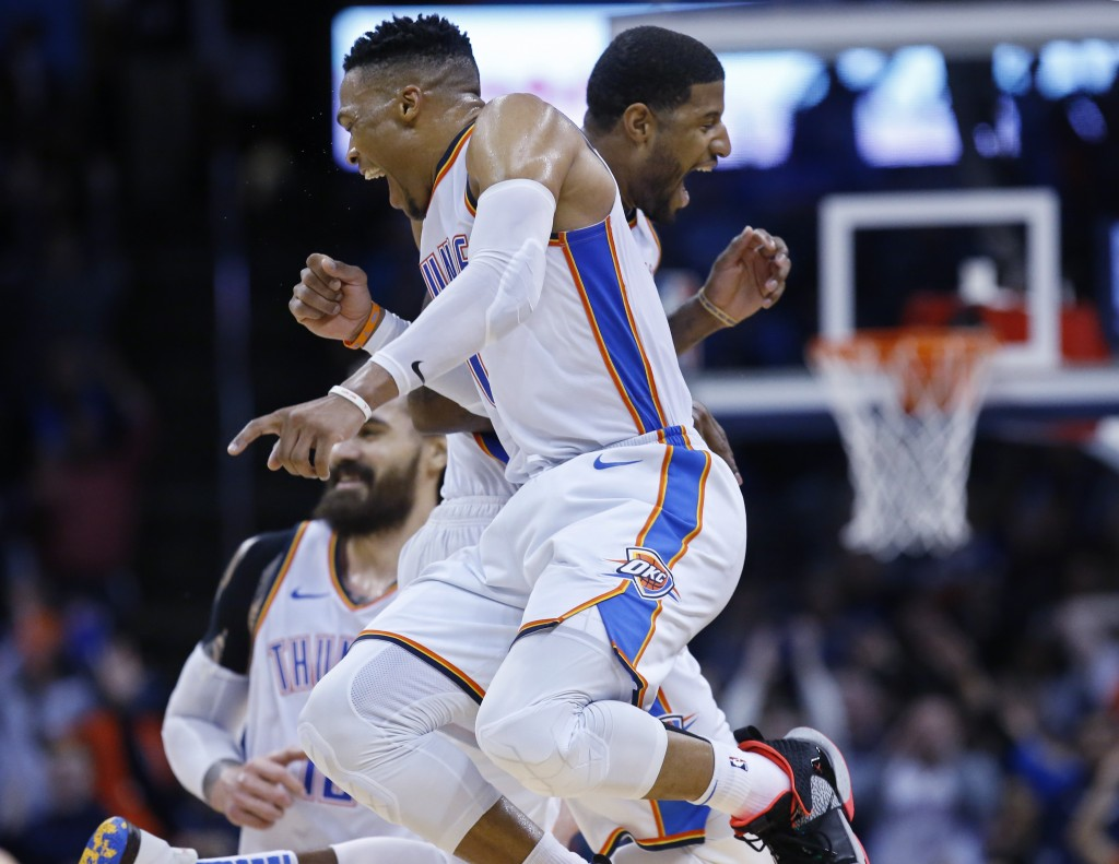 Oklahoma City Thunder guard Russell Westbrook, left, and forward Paul George, right, celebrate late in the second half of an NBA basketball game again