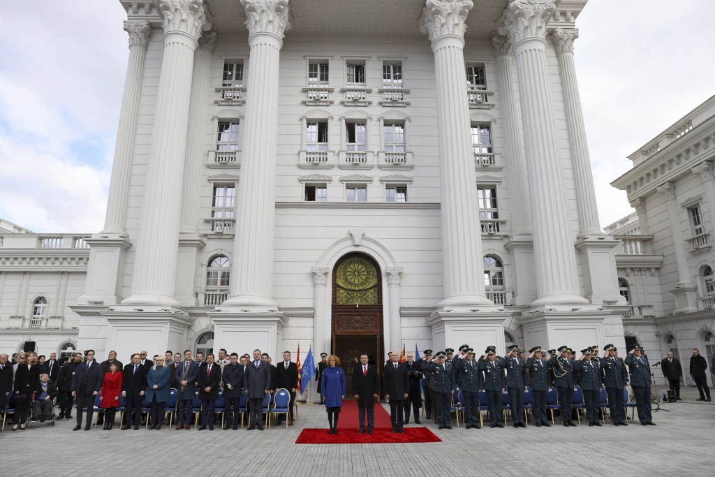 Macedonian officials take part at a ceremony in front of the government building in Skopje, Tuesday, Feb. 12, 2019. Macedonian authorities began remov...