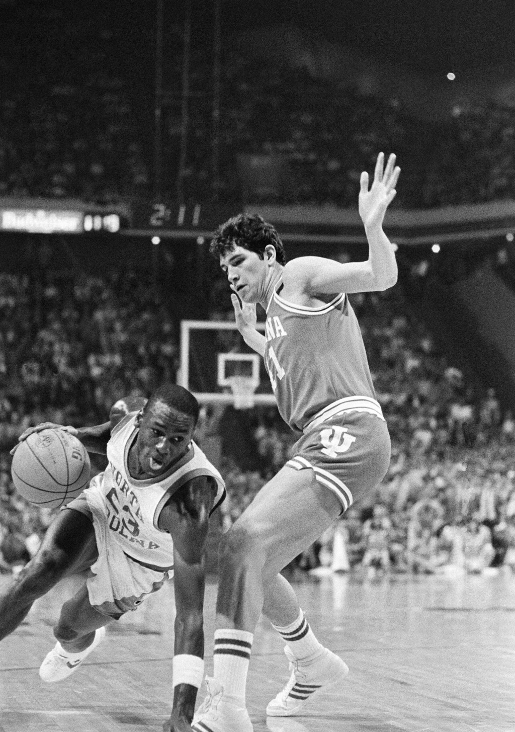 File-This March 23, 1984, file photo shows North Carolina forward Michael Jordan, trying to drive past Indiana forward Mike Giomi at Omni Coliseum in ...