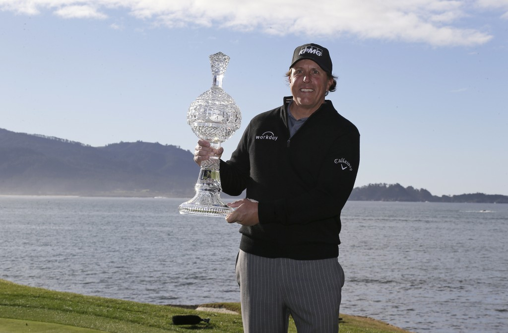 Phil Mickelson poses with his trophy on the 18th green of the Pebble Beach Golf Links after winning the AT&T Pebble Beach Pro-Am golf tournament Monda...