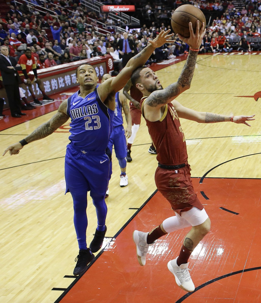 Houston Rockets guard Austin Rivers, right, drives to the basket as Dallas Mavericks guard Trey Burke defends during the first half of an NBA basketba