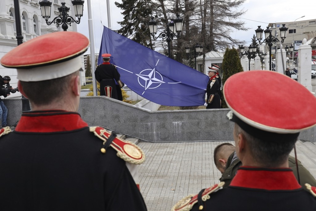 Macedonian soldiers raise the NATO flag in front of the government building during a ceremony in Skopje, Tuesday, Feb. 12, 2019. Macedonian authoritie...