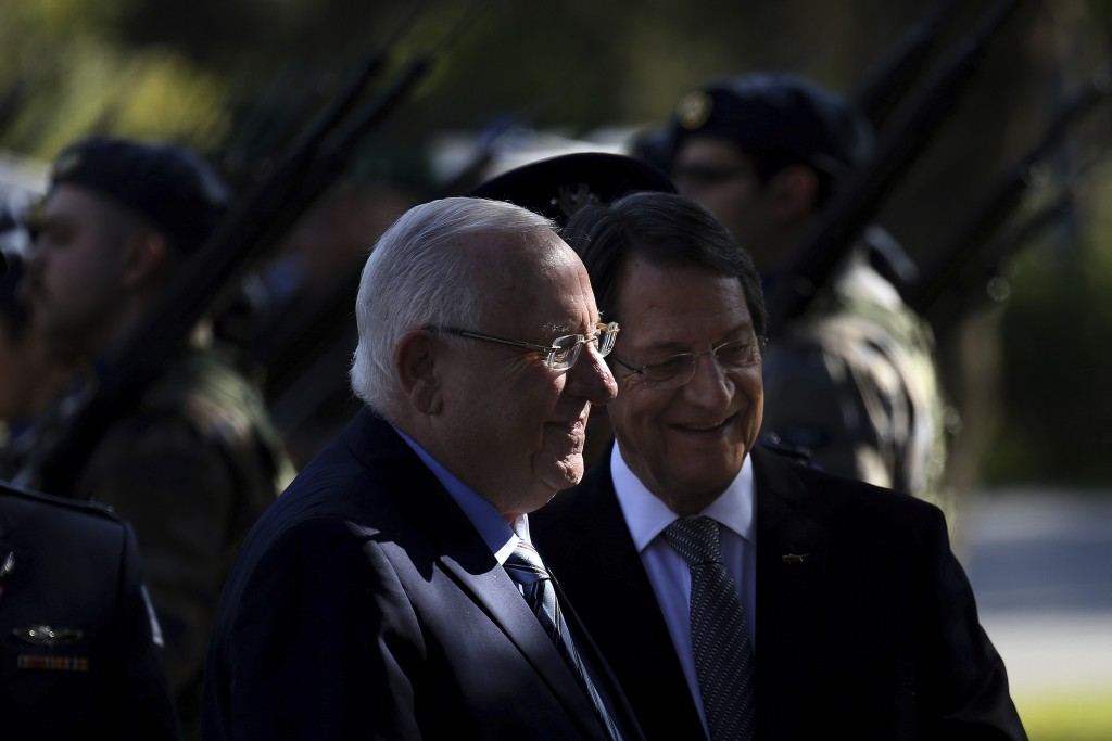 Cyprus' president Nicos Anastasiades and Israel's President Reuven Rivlin, left, review a military guard of honor during a welcoming ceremony at the p...