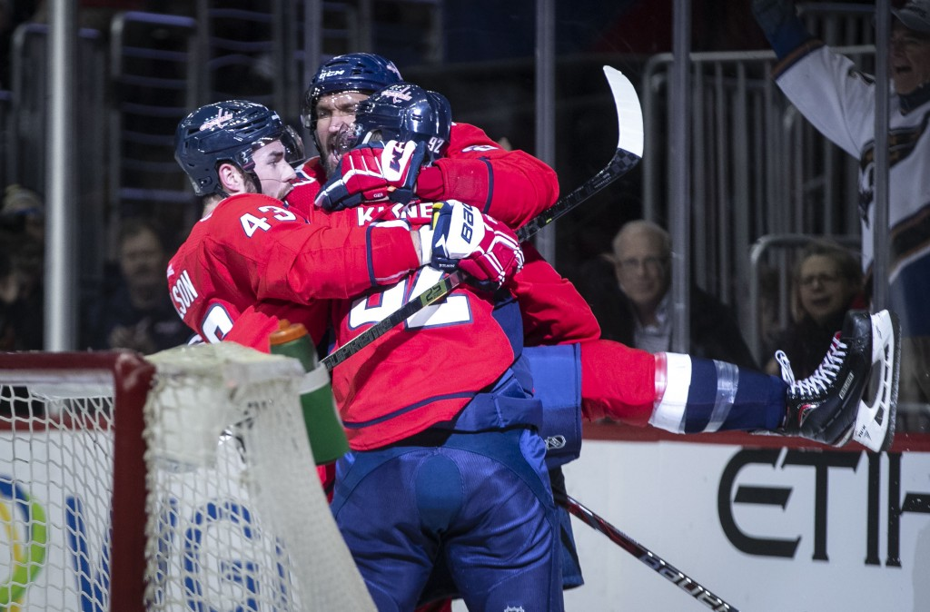 Washington Capitals center Evgeny Kuznetsov (92), of Russia, celebrates after scoring with right wing Tom Wilson (43) and left wing Alex Ovechkin (8),...
