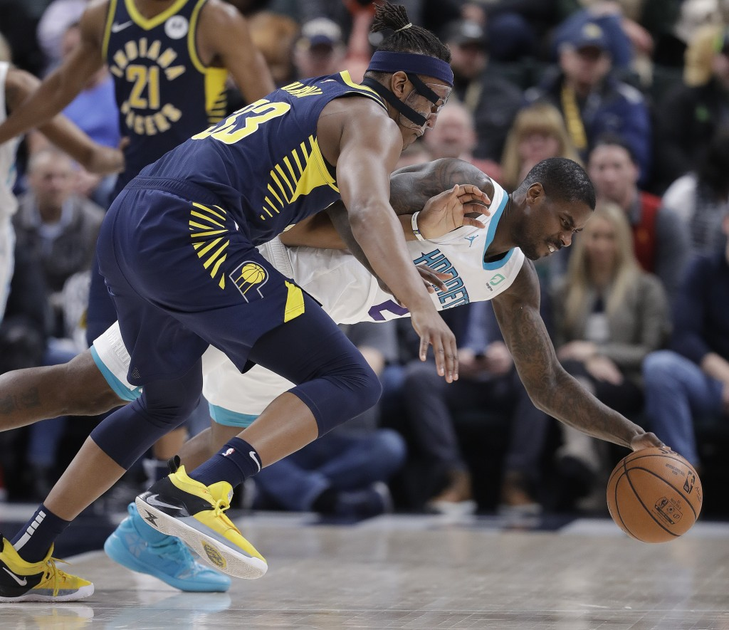 Indiana Pacers' Myles Turner, left, and Charlotte Hornets' Marvin Williams, right, battle for a loose ball during the first half of an NBA basketball ...