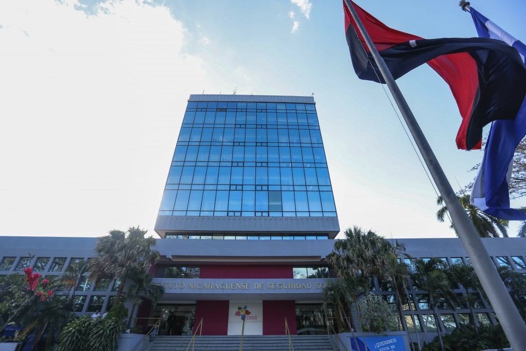 In this Feb. 8, 2019 photo, a Sandinista National Liberation Front ruling party banner and a national flag fly outside the Social Security Institute, ...