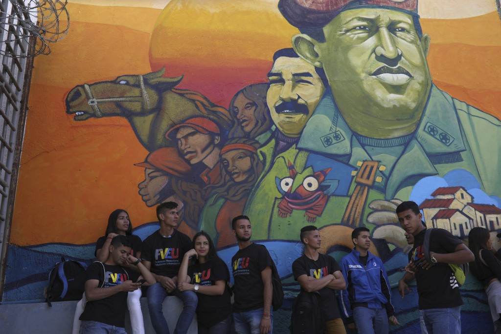 Pro-government university students stands next to a mural with the images of Venezuela's late president Hugo Chavez and President Nicolas Maduro durin