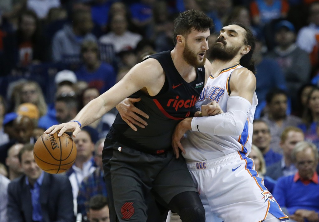 Portland Trail Blazers center Jusuf Nurkic, left, drives around Oklahoma City Thunder center Steven Adams, right, in the first half of an NBA basketba...